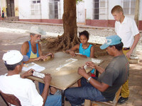 . A group of people enjoy an outdoor game of dominoes in Cuba. Photo courtesy of Victor Block.