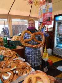 A vendor in the Salzburg, Austria, food market offers a pretzel. Photo courtesy of John Blanchette.
