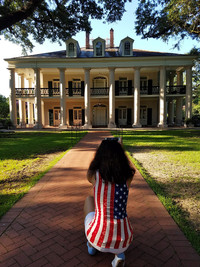 A visitor kneels to get a picture of Oak Alley Plantation near New Orleans. Photo courtesy of Jim Farber.