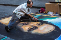 "A street artist in Venice, Italy, draws the ""Mona Lisa"" in chalk on asphalt. Photo courtesy of Mihai Andritoiu/ dreamstime.com."