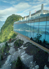 Dramatic cliff-side views of Lake Lucerne in Switzerland reflect off windows of the Burgenstock Hotel. Photo courtesy of Athena Lucero.