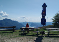 A hiker stops at Alpe Rompiago to take in views above Switzerland's Lake Lugano. Photo courtesy of Athena Lucero.