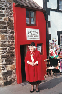 A tour guide stands in front of the smallest house in Great Britain, located in Conwy, Wales. Photo courtesy of Sharon Whitley Larsen.