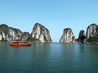 Natural formations dwarf the boats that bring passengers to see them in Vietnam's Ha Long Bay. Photo courtesy of Victor Block.