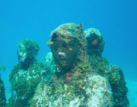 Viewers of sculptures at Mexico's Cancun Underwater Museum must dive to see them or look through a glass-bottom boat. Photo courtesy of Nialldunne24/Dreamstime.com.