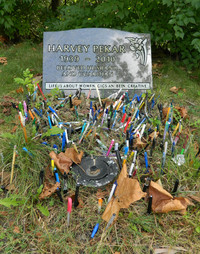 Fans of cartoonist Harvey Pekar use colored pens to decorate his burial spot at the Lakeview Cemetery in Cleveland, Ohio. Photo courtesy of Steve Bergsman.