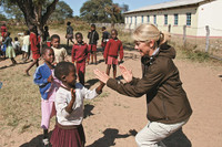 A member of an Overseas Adventure Travel tour group interacts with children in Zimbabwe. Photo courtesy of the Grand Circle Corp.