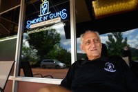 Gregory Ionadi, 75, sits in front of Smoke N' Guns, which he owns with his son, Gregory 'Gooch' Ionadi. Photo credit Justin Merriman